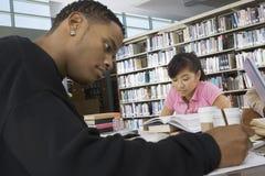 学习在大学图书馆里的学生 免版税图库摄影