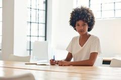 学习在校园桌上的确信的年轻非洲女学生 免版税库存照片