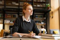 学习在桌上的沉思红发十几岁的女孩 免版税库存图片