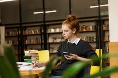学习在桌上的沉思红发十几岁的女孩 库存照片
