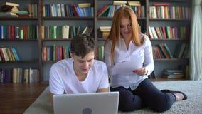 学习在膝上型计算机的男性和女学生 一起学会的学生4对k夫妇  群策群力工作的两名学生 股票录像