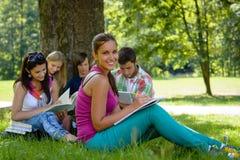学习在草甸的学员在公园十几岁 免版税库存照片