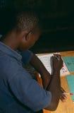 学习在选件类,卢旺达的男孩。 免版税库存图片