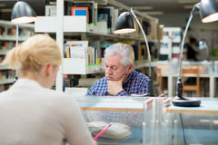 学习在青年人之中的老人在图书馆里 库存照片