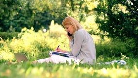 学习年轻女人的学生,当坐在公园时 美丽的庭院 娱乐活动在春天和夏天 影视素材