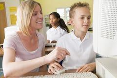学习教师的计算机男小学生 免版税库存图片
