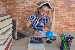 学习教训的年轻可爱的学生女孩 在家坐在书桌的女孩,做家庭作业 免版税库存照片