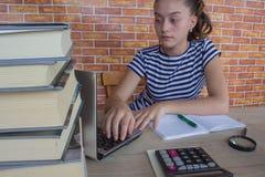 学习教训的年轻可爱的学生女孩 在家坐在书桌的女孩,做家庭作业 免版税库存图片