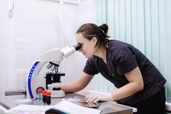 学习新的物质或病毒在显微镜的女性科学家 库存照片