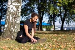 学习瑜伽的美丽的女孩在公园 库存照片