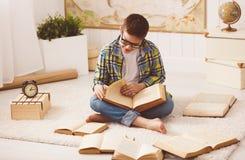 学习男孩的少年,阅读书,为检查做准备在hom 免版税库存图片