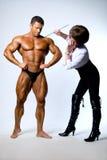 学习男性身体肌肉人的妇女 免版税库存照片