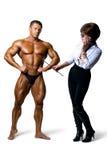 学习男性身体肌肉人的美丽的妇女 免版税库存图片