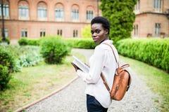 学习的开始 在校园里的可爱的非洲女性大学生 免版税库存照片