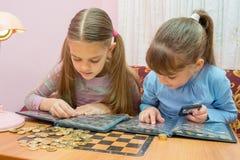 学习硬币册页的两个孩子 免版税库存照片