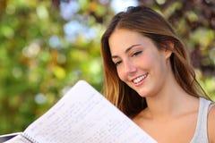 学习美丽的少年的女孩读室外的笔记本 免版税库存照片