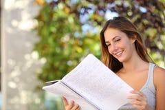 学习美丽的少年的女孩读室外的笔记本 图库摄影