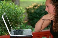 学习膝上型计算机的特写镜头青少年的女孩户外 库存图片