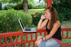 学习膝上型计算机的青少年的女孩户外 免版税库存图片