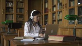 学习题目的年轻美丽的妇女,坐在与膝上型计算机的桌上在图书馆里 股票录像