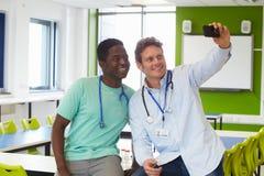 学习医学的学生和家庭教师采取Selfie 图库摄影