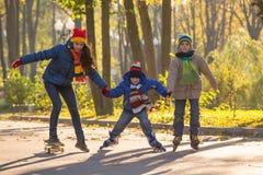 学会三个的孩子在秋天公园乘坐在直排轮式溜冰鞋和s 图库摄影