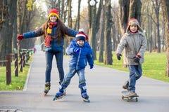学会三个的孩子在秋天公园乘坐在直排轮式溜冰鞋 库存照片