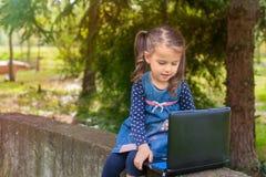 学会与片剂个人计算机的滑稽的小女孩在公园 免版税图库摄影