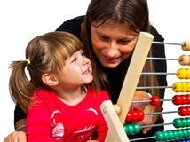 学会与算盘的母亲和女儿算术 免版税库存照片