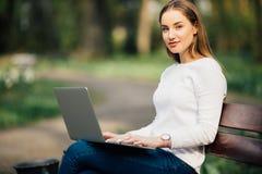 学会与膝上型计算机的愉快的学生少年女孩在一条长凳在大学里 免版税库存图片