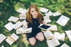 学会与ebook读者和书的妇女 在现代教育技术和传统方式方法之间的选择 举行d的女孩 库存图片