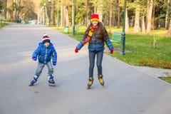 学会两个的孩子在秋天公园乘坐在直排轮式溜冰鞋 免版税库存图片