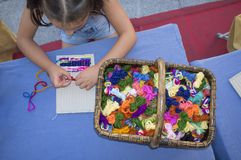 学会儿童的女孩使用纸板编织机 免版税图库摄影