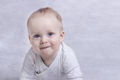 学会可爱的男婴爬行和使用 爬行在床上的逗人喜爱的笑的孩子 复制空间 库存照片
