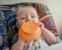 学会可爱的婴孩第一次哺养自己 免版税库存照片
