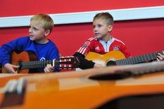 学会吉他的孩子 库存照片