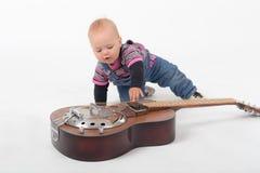 学会吉他的婴孩 免版税库存图片
