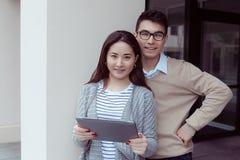 学会和看在片剂个人计算机的两名可爱的学生室外的校园 免版税库存照片