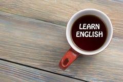 学会在咖啡杯写的英国文本 办公桌台式视图 免版税库存照片