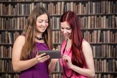 学会在图书馆里的两个学生女孩 免版税库存图片