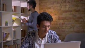学会在大学图书馆里的两名文化上不同的学生特写镜头射击户内 在网上学习印度的男性  股票视频