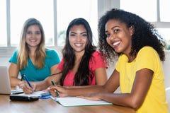 学会在教室的三个女学生 免版税库存图片