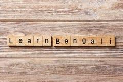学会在木刻写的孟加拉词 学会在桌上的孟加拉文本,概念 免版税库存照片