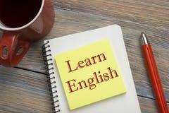 学会在笔记本页、红色铅笔和咖啡杯写的英国文本 办公桌台式视图 免版税库存图片