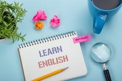学会在笔记本页、红色铅笔和咖啡杯写的英国文本 办公桌台式视图 库存照片