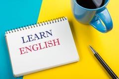 学会在笔记本页、红色铅笔和咖啡杯写的英国文本 办公桌台式视图 库存图片