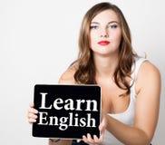 学会在虚屏写的英语 有拿着个人计算机片剂的光秃的肩膀的美丽的妇女 技术,互联网 库存照片