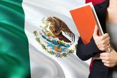 学会墨西哥语言概念 与墨西哥旗子的年轻女人身分在背景中 拿着书,桔子的老师 免版税库存照片