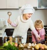 学会如何的两个妹烹调 免版税图库摄影