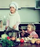 学会如何的两个妹烹调 免版税库存照片